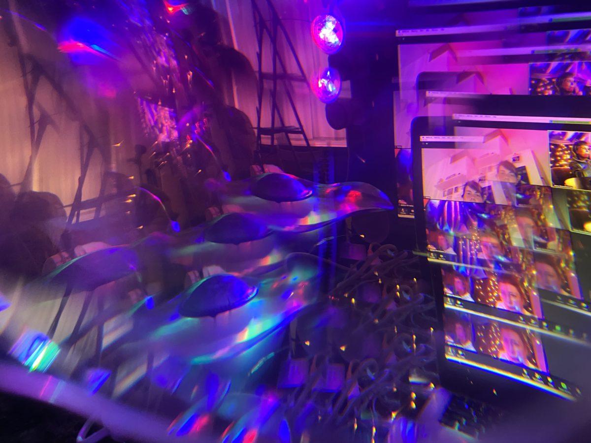 durch ein Prisma verzerrt sind ein Bildschirm und viele lila und pinke Lampen zu sehen.