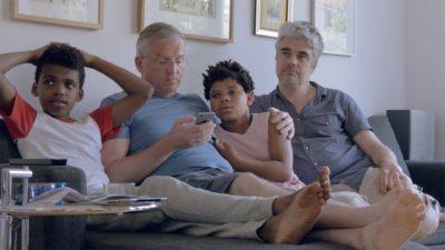 Zwei weiße grauhaarige Männer und zwei Kinder mit dunkler Hautfarbe sitzen zusammen auf einem Sofa.