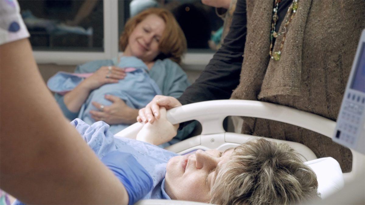 Vorn im Bild liegt eine Person erschöpft im Krankenhausbett, im Hintergrund ist eine lächelnde Person mit einem Baby auf dem Arm zu sehen