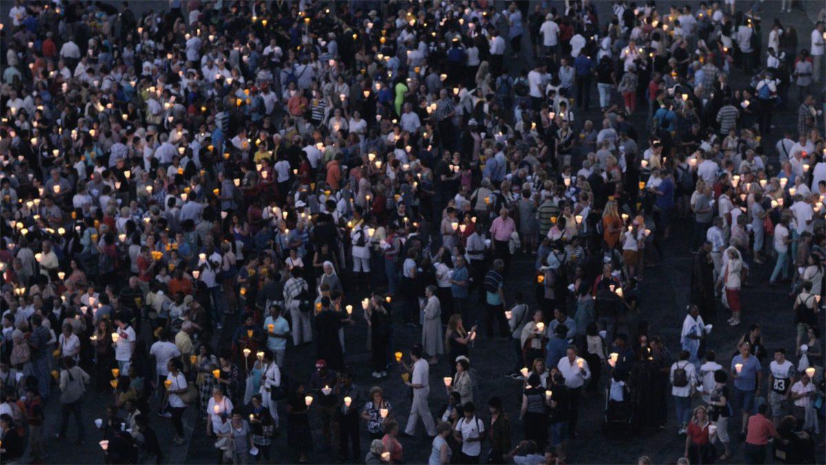 In einer Menschenmenge stehen viele Personen mit Kerzen in der Hand.