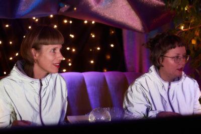 Zwei Personen mit weiß reflektierenden Jacken sitzen in einer Höhle aus Lichtern und glitzerndem Stoff.