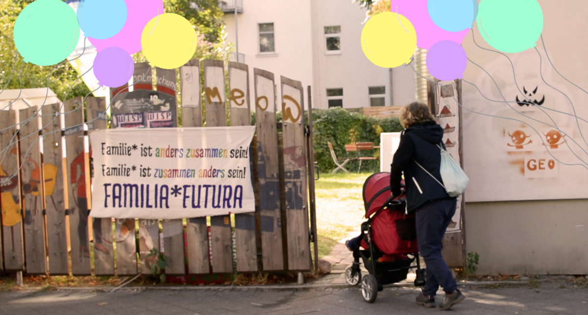 Eine Person schiebt einen Kinderwagen in ein Holztor. Am Holztor hängt ein weißer Stoff mit der Aufschrift: Familie ist zusammen anders sein. Familie ist anders zusammen sein.